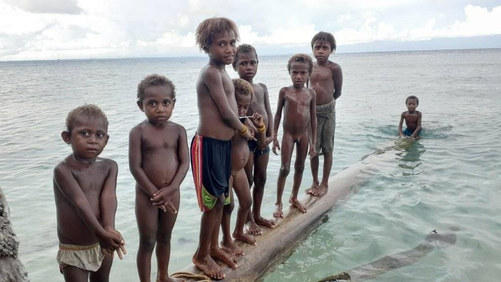 A dozen children floating on a log in the bay